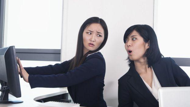 Dos mujeres en la oficina, una de ellas intenta mirar la pantalla de la otra.