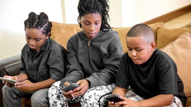 tres niños usando celulares