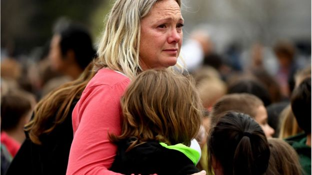 A school staff member comforts a child after the shooting