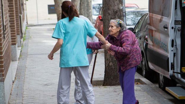 Una enfermera ayuda a una persona mayor en una casa de cuidado de ancianos en Madrid.