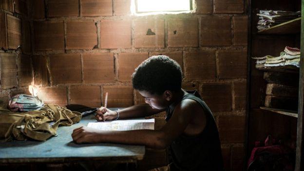 Un niño en una casa precaria haciendo tarea.