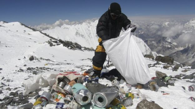 Nepalese sherpa picking up trash on Everest