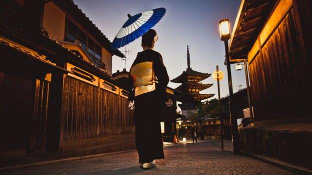 Mujer japonesa recorriendo calles poco iluminadas.