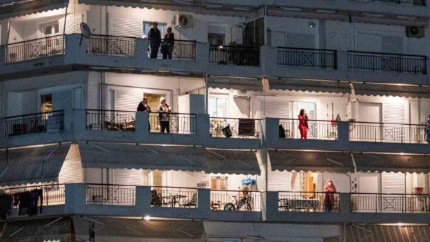 Un edificio de apartamentos con personas en cuarentena asomadas al balcón