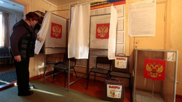 Una oficial electoral supervisa las cabinas de votación antes de las elecciones presidenciales rusas