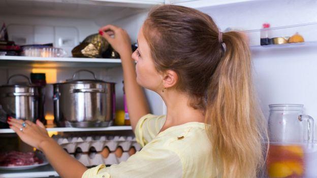Mujer guarda alimentos en una nevera