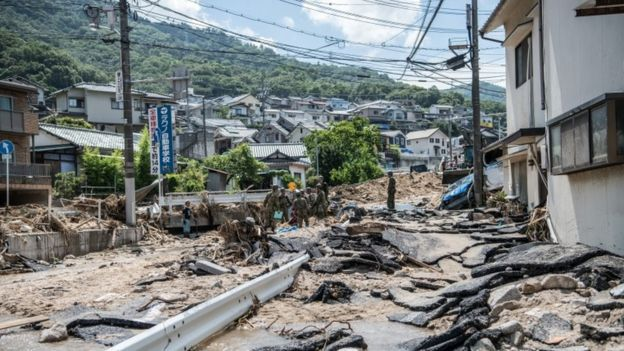 Soldiers work to clear a road following a landslide, on July 10, 2018 in Yanohigashi near Hiroshima, Japan