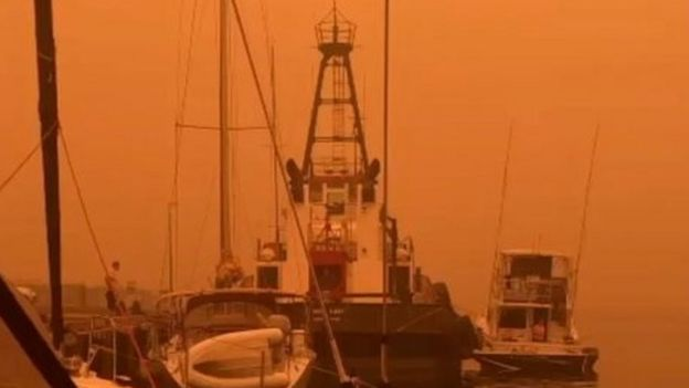 An orange sky shrouds boats at a wharf in Eden, NSW