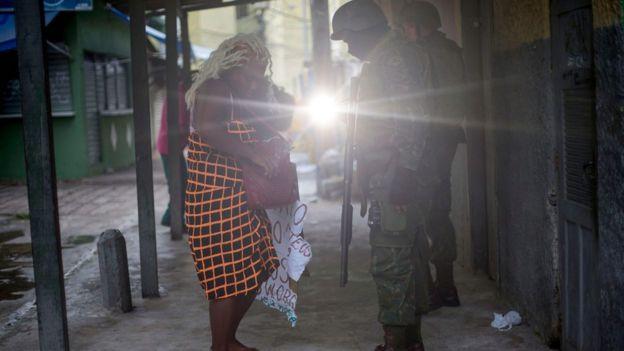 Soldados revistam uma mulher na entrada da comunidade Cidade de Deus