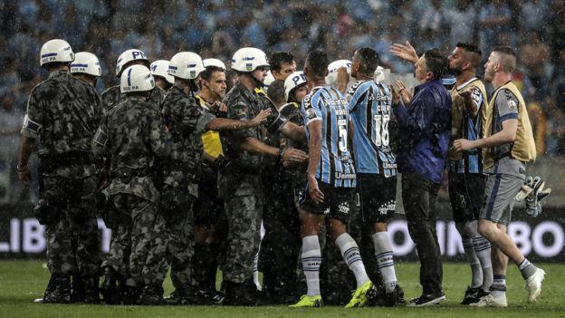 Los jugadores de Gremio rodean al árbitro Andrés Cunha.