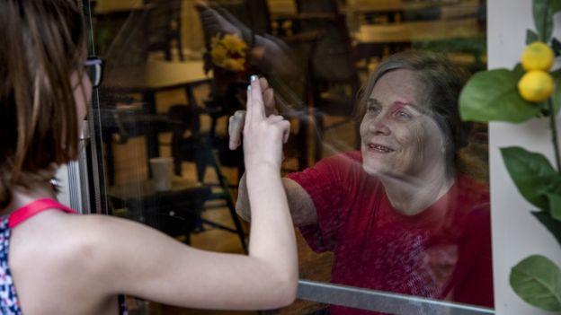 Abuela y nieta detrás de una ventana.
