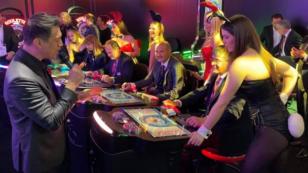 Women dressed as Playboy bunnies watch people use gambling machines