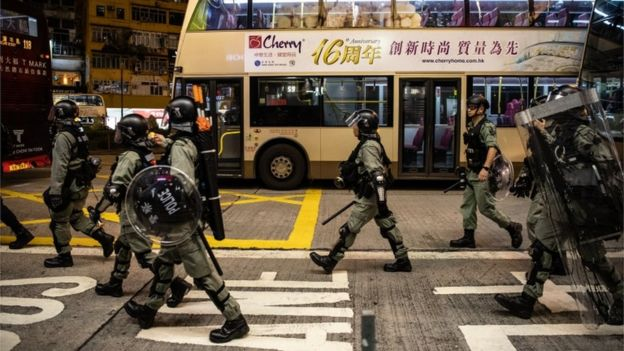 Riot police walk past a bus, Hong Kong, 5 October 2019