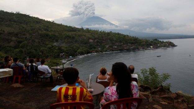 旅客从艾眉湾附近的咖啡厅眺望冒着浓烟的火山。