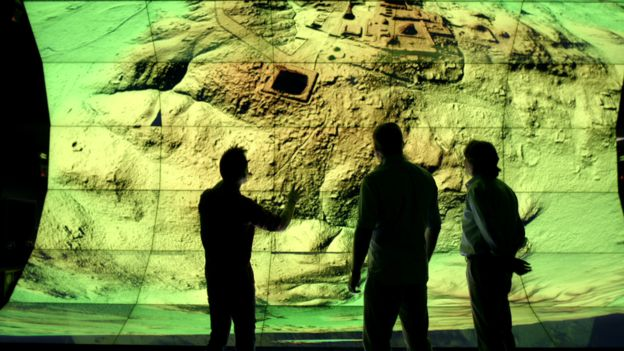 Three surveyors looks at a large digital screen showing a Lidar image of a Mayan city.
