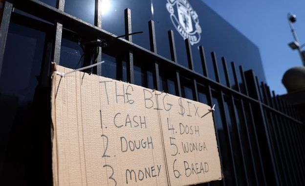 A protest sign outside Manchester United's Old Trafford ground