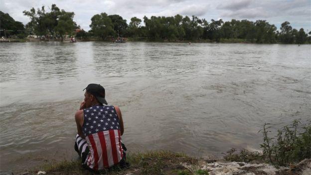 Migrante en la frontera con una camisa con la bandera estadounidense.