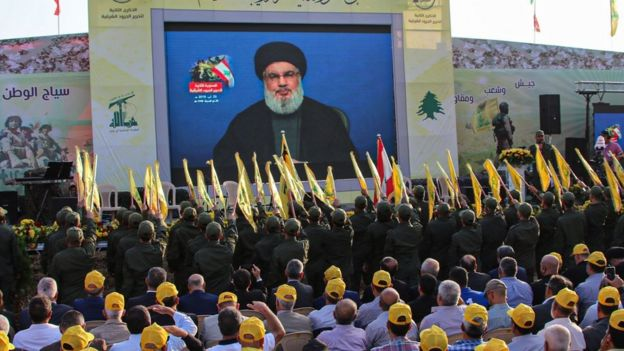 Hezbollah members salute as the Lebanese group's leader, Hassan Nasrallah, addresses a rally in al-Ain (25 August 2019)