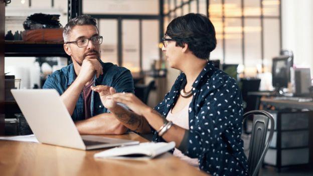 Dos personas hablando en un entorno laboral.