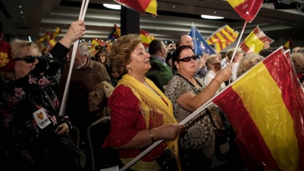 Supports of Spanish Prime Minister Mariano Rajoy wave flags