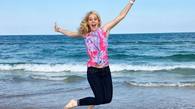 Victoria leaps into the air in front of the ocean