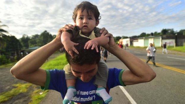 A Honduran migrant holds a baby as he takes part in a caravan heading to the US on October 21, 2018.