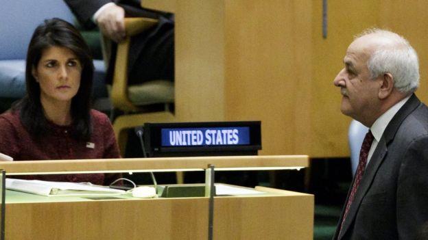 El enviado de los palestinos a la ONU, Riad Mansour, camina frente a la embajadora de Estados Unidos, Nikki Haley, durante la sesión de la Asamblea General.