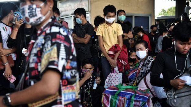 Người di dân Myanmar, Lào và Cambodia chen nhau đợị xe buýt rời khỏi Bangkok Thái Lan để về nhà khi bệnh dịch lây lan nhanh ở nước này