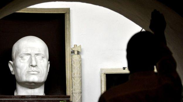 مناصر يميني متطرف يؤدي التحية الفاشية عند مقربة من ضريح موسوليني في بريدابيو