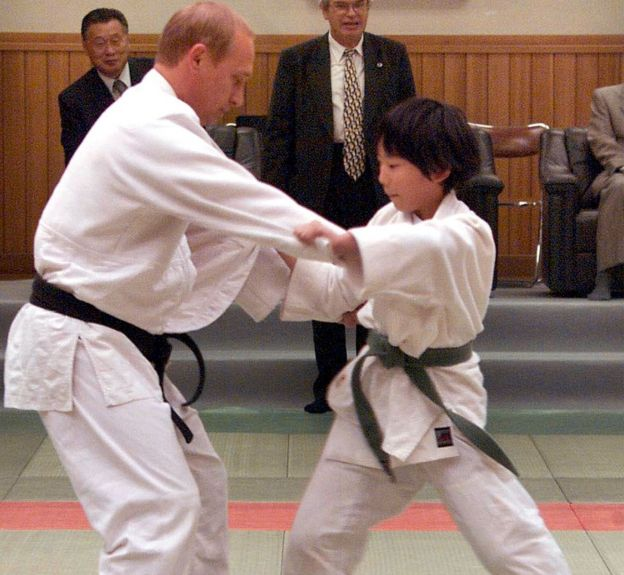 Russian President Vladimir Putin (L) in judo outfit fights against 10-year-old Japanese schoolgirl Natsumi Gomi as he visits a Tokyo judo training center Kodokan hall 05 September 2000. Putin, who has a black belt in the sport, was thrown over her shoulder onto the mat.