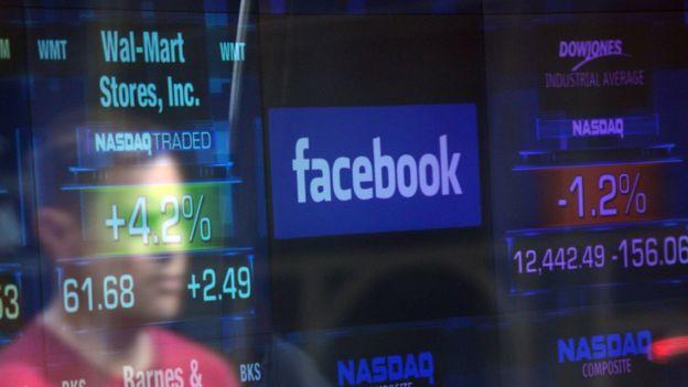 Logo do Facebook em meio a dados de bolsa de valores em Nova York