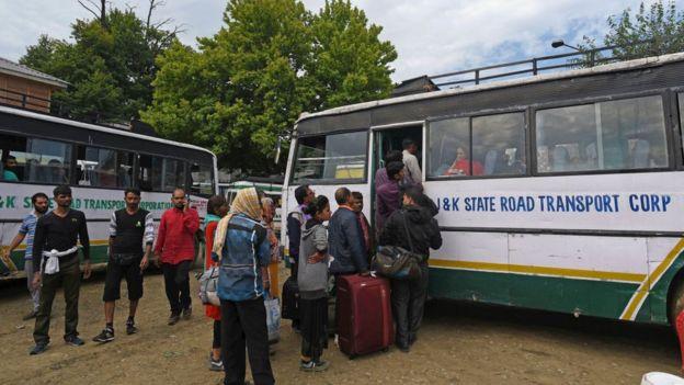 Туристы и паломники садятся в автобус в Кашмире