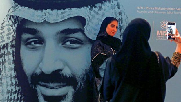 Mulheres fazem 'selfie' com cartaz de Bin Salman