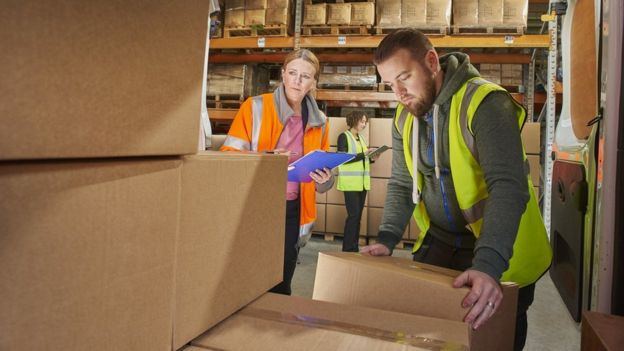 Man taking parcels out of van in warehouse