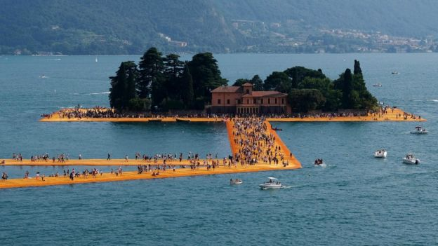 "A general view shows people walking ""The Floating Piers"" by Christo and Jeanne-Claude on Lake Iseo, 3 July 2016"