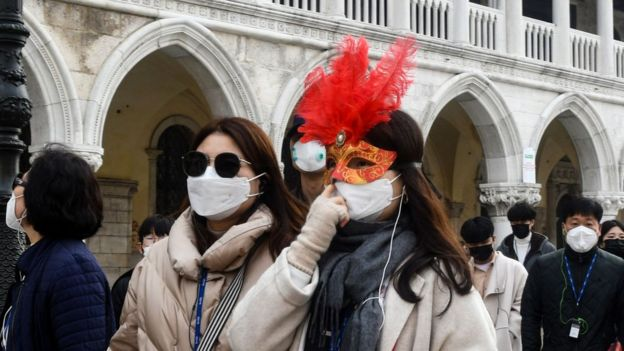 Tourists wearing protective facemasks and a Carnival mask visit the Piazza San Marco, in Venice