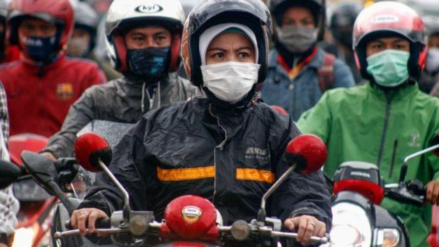 Pengendaa motor mengenakan masker