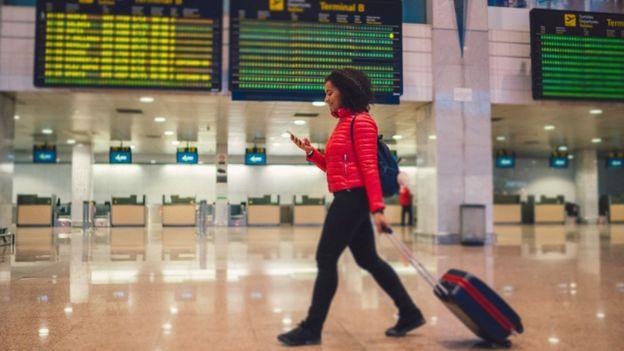 Una mujer pasea en un aeropuerto.