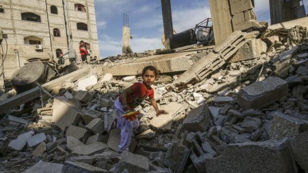 Filistinli bir kız çocuğu Gazze'de yıkılan bir evin enkazı üzerinde yürüyor