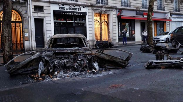 A picture shows charred cars in a street of Paris on December 2, 2018, a day after clashes during a protest of Yellow vests (Gilets jaunes) against rising oil prices and living costs