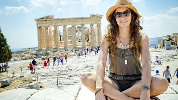Una joven sentada frente al Partenón.