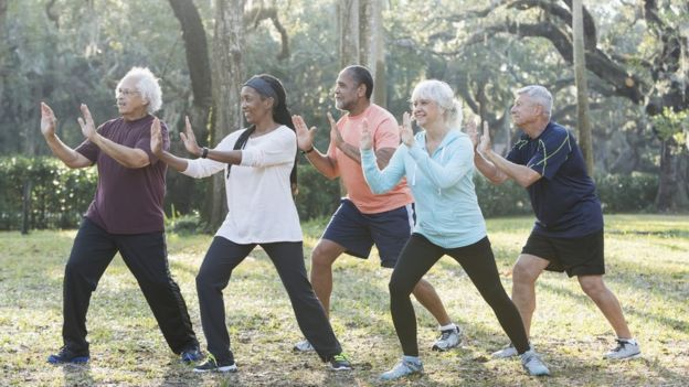 Adults doing taichi outdoors.  Photo by kali9 / Getty Images.