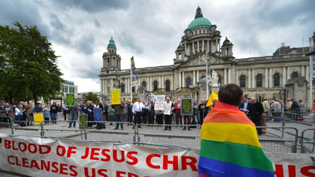 A man in a rainbow flag watches a Christian protest against the Belfast Pride parade