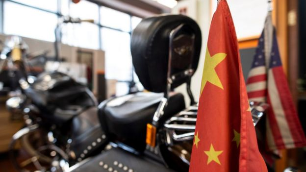 Chinese and US flags are seen on a Harley-Davidson motorcycle in the maintenance room of a dealership in Shanghai on August 24, 2018.