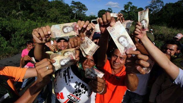 Gente con billetes de 100 bolívares