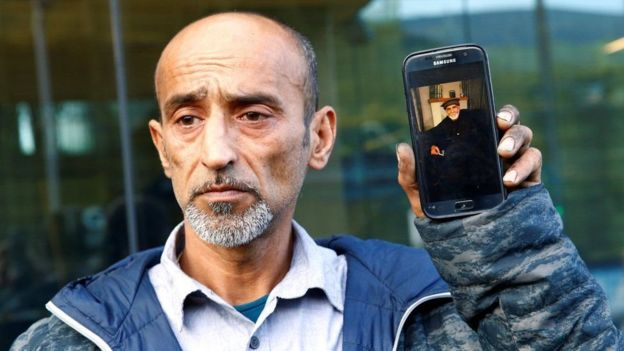 Omar Nabi oo gacanta ku haya telefan uu ka dhex muuqdo aabbihiis Daoud, bannaanka maxkamadda.