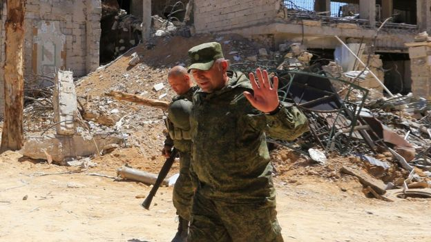 Russian forces walk past damaged buildings in Douma on the outskirts of Damascus on April 16, 2018