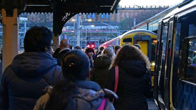 Passengers queue to board a train