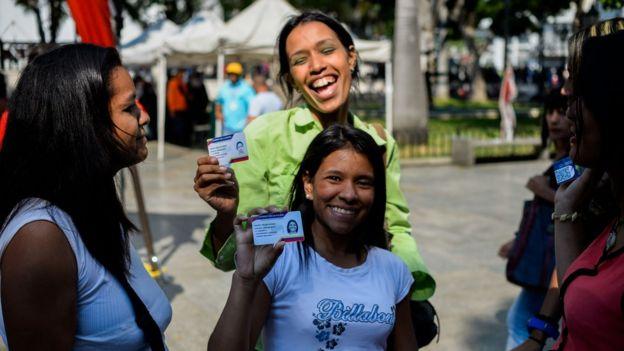 Dos mujeres sonríen a la cámara mientras muestran su carnet de la patria.