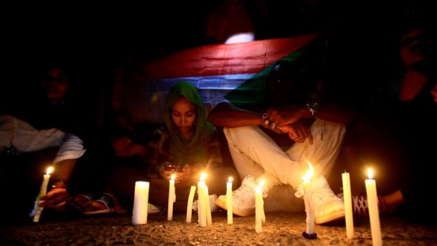 Sudanese protesters take part in a vigil in the capital Khartoum to mourn dozens of demonstrators killed in the raid on the Khartoum sit-in, 13 July